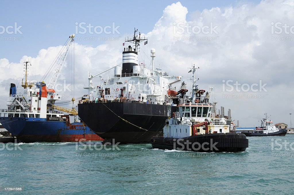Tugboat pulling a cargo ship royalty-free stock photo