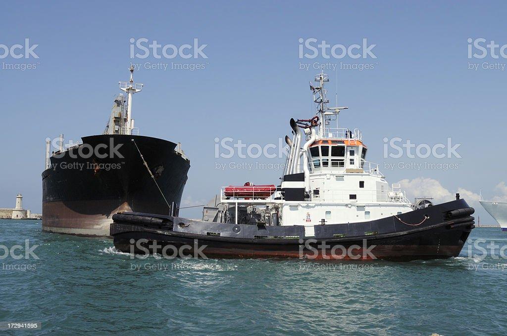 Tugboat pulling a cargoship inside the harbor royalty-free stock photo