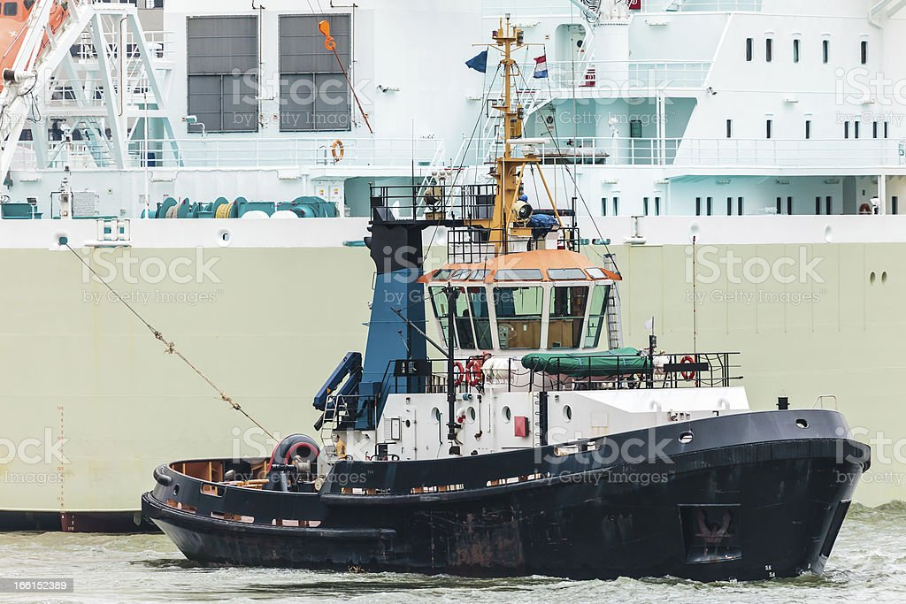 Tugboat pulling a large ship royalty-free stock photo