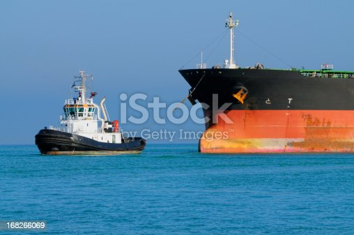 istock Tugboat Pulling Industrial Ship 168266069