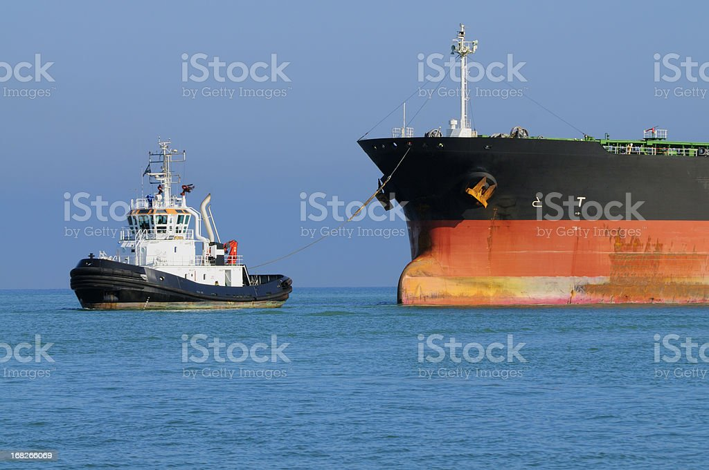 Tugboat Pulling Industrial Ship stock photo