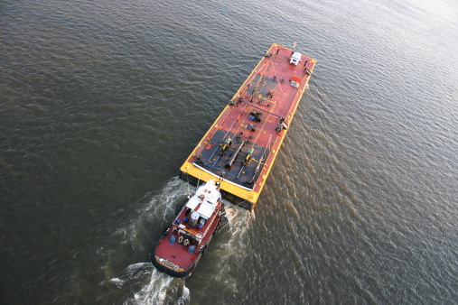 Tugboat pushing a barge up a river.
