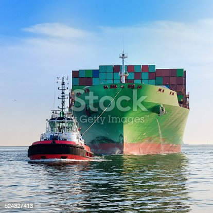 front view on a tugboat towing a large cargo container ship with piled up cargo containers on deck into harbour