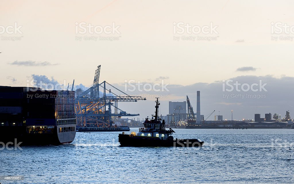full length shot of a tugboat towing cargo container ship in harbour...