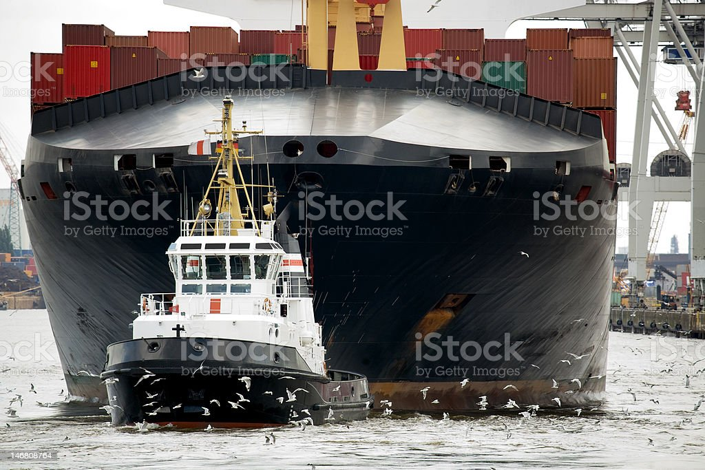 tugboat towing freighter in harbor stock photo