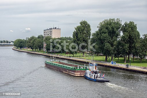 Tugboat with empty cargo vessel at Dutch Amsterdam Rijn canal near city Utrecht