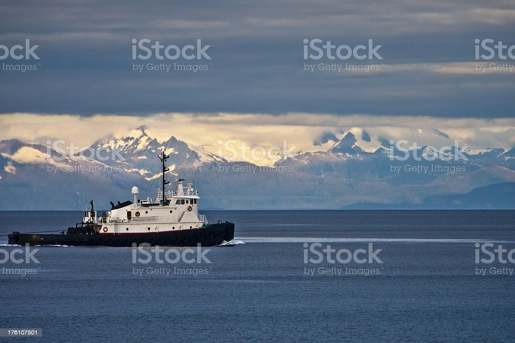 Tugboat works Inside Passage of Alaska with mountains as backdrop royalty-free stock photo