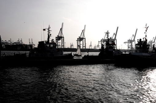 tugboats and cranes at sunset