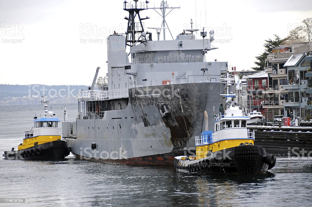 Tugboats guiding damaged research vessel to locks stock photo