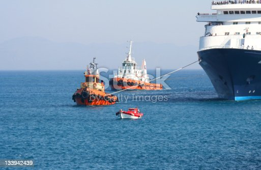 Tugboats and a pilot boat maneuvering a large tourist ferry into a harbour on the Greek island of Rhodes. It's a hot, summer day with blue, cloudless sky. Mountains are visible on the horizon. Dominant colors: blue, red, orange, black, white.