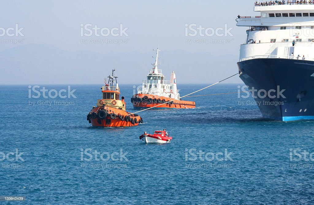 Tugboats towing a ferry into a harbor stock photo