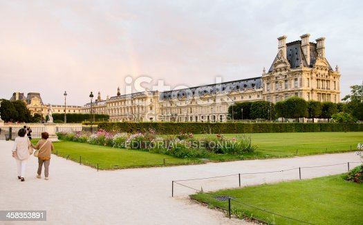 Paris, France - September 7, 2013: Tourists are walking in the tuileries gardens in Paris; some are photographing the Louvre and a rainbow above.