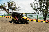 Tuk tuk carries passengers on the road against the sea. Andaman and Nicobar Islands, port Blair. India. January 12, 2018