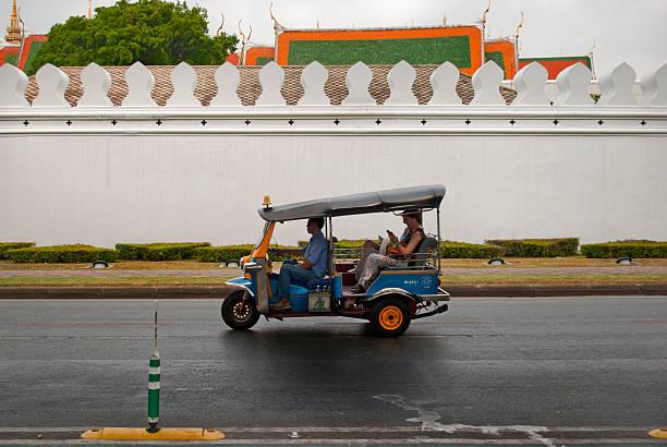 Tuk tuk driver outside of the Grand Palace stock photo