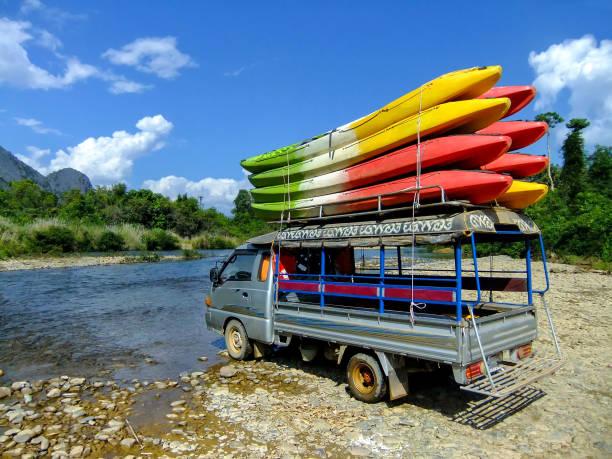 tuk-tuk geladen mit kajaks am nam song river, laos - vang vieng stock-fotos und bilder