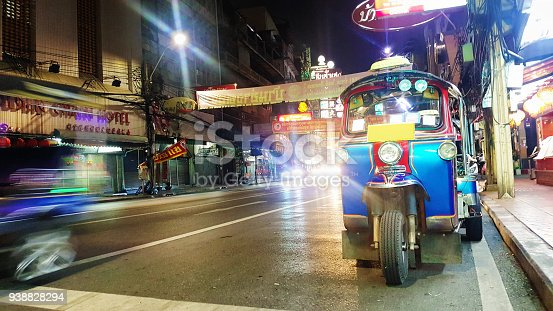 Tuk-tuk motorized rickshaw parked in Bangkok's Chinatown at night with light traffic coming from the back.