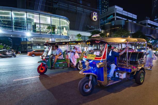 Tuk-Tuk on street at night with customers. stock photo