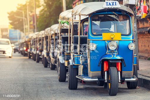A row of tuk-tuks parked along a city street in central Chiang Mai, Thailand.