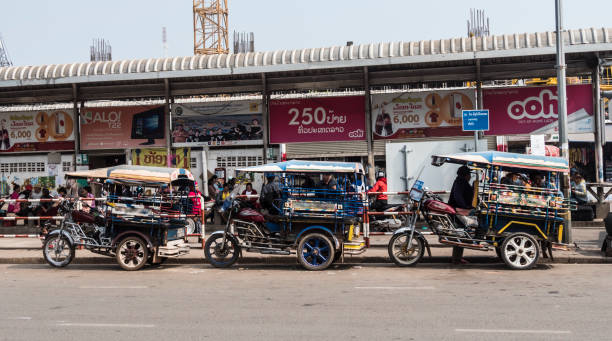 Tuktuks lined up in a row VIENTIANE, LAOS - FEBRUARY 6, 2018: Tuktuks lined up in a row at Vientiane, Laos. three wheel motorcycle stock pictures, royalty-free photos & images