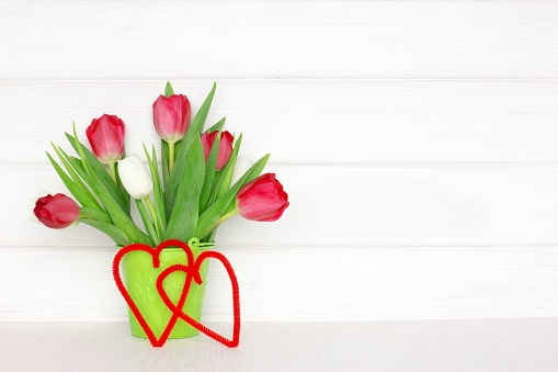 Tulip flower bouquet with two hearts on wooden table near white wood wall. Valentine Day concept with copy space. Spring rustic background
