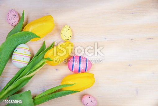 921112244 istock photo Tulip Flowers and Easter Eggs on Wooden Background 1209325943