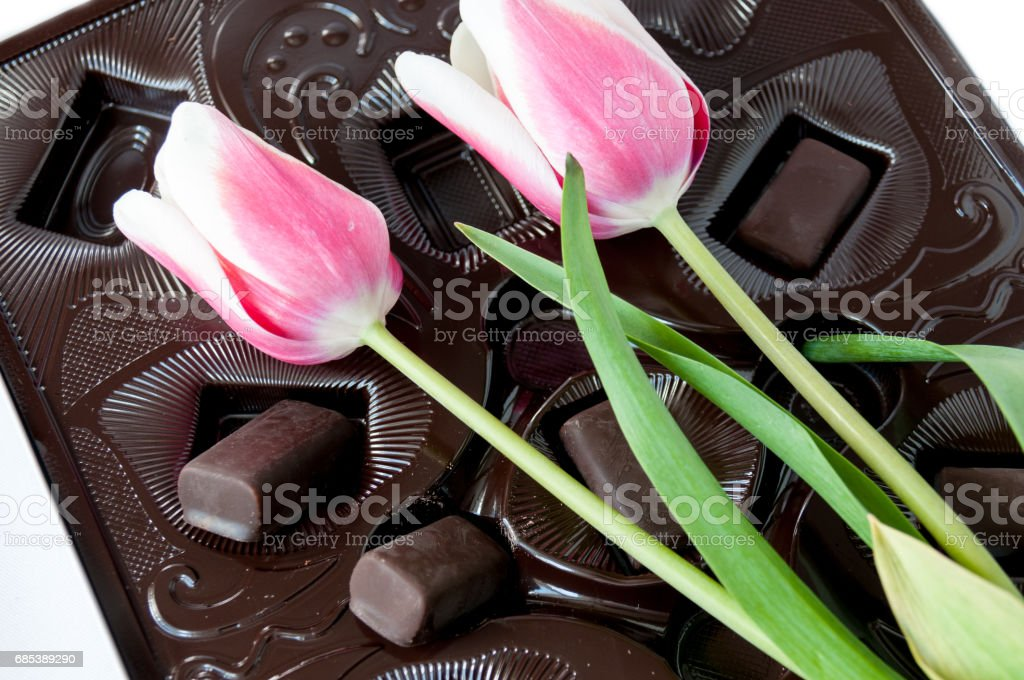 Tulips and chocolate sweets on a brown background foto de stock royalty-free