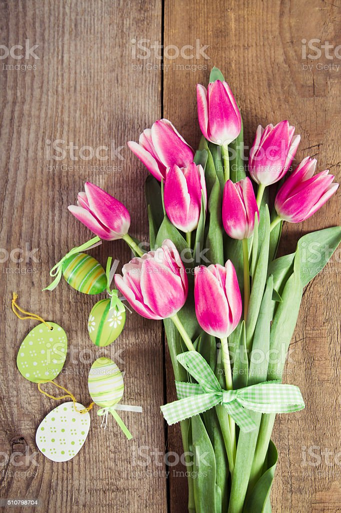 tulips and decorated eggs on wood stock photo