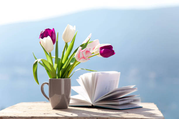 Tulips and opened book at wooden table outdoors. Spring still life at sea beach. Blooming flowers stock photo