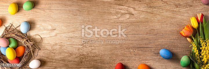 922843504 istock photo Tulips and painted eggs in nests on vintage plank 1132117792
