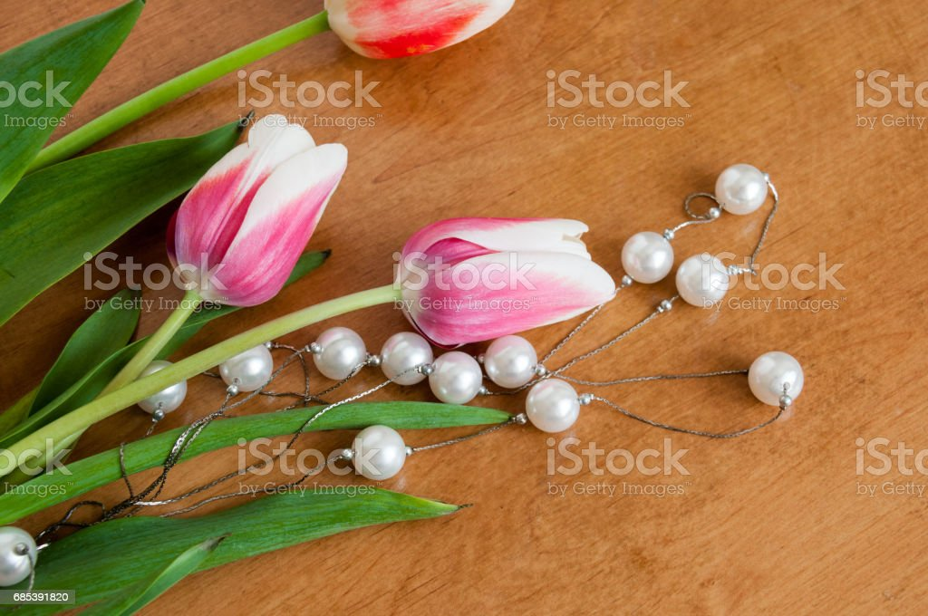 Tulips and white pearls lie on the table royalty-free stock photo