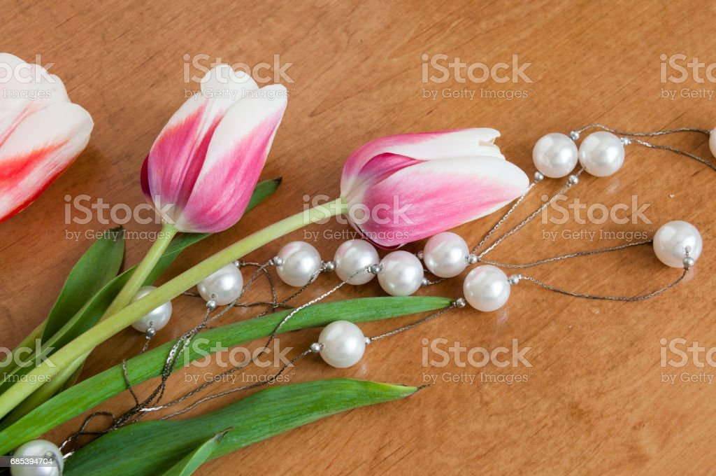 Tulips and white pearls lie on the table foto de stock royalty-free