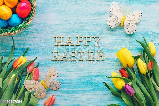 Tulips, Easter eggs and butterflies on a blue background with