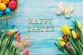 Tulips, Easter eggs and butterflies on a blue background with 'Happy Easter' text