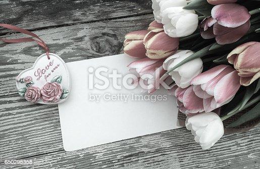 istock Tulips flowers bunch on dark barn wood planks background 650298358