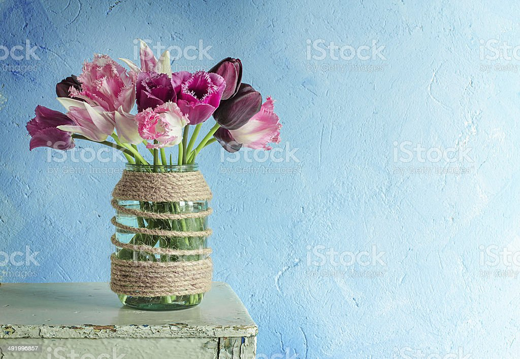 Tulips in a decorated glass jar stock photo