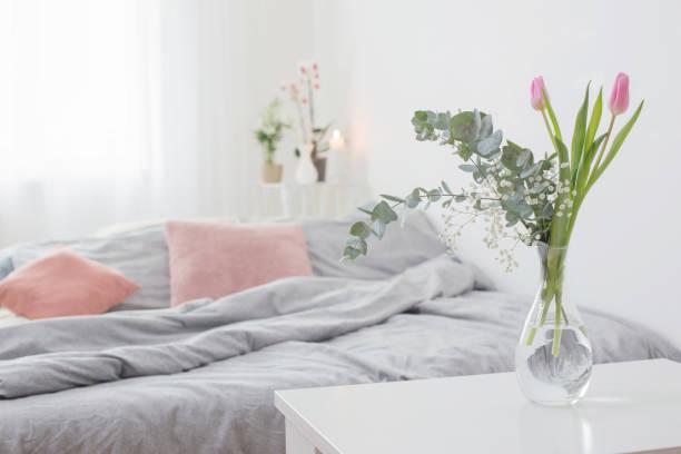 tulips in vase in cozy bedroom stock photo