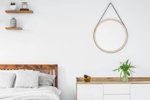 스 칸디 나 비아 스타일 옷장, 나무 선반 식물 화병과 화이트 거실 인테리어에 둥근 거울에 튤립 - 옷서랍 뉴스 사진 이미지