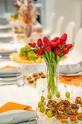 vase with a bouquet of red tulips on the festive table. serving the table with appetizers, canapes, salads in jars. Catering. restaurant business.