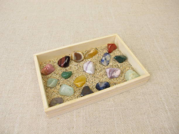 Tumbled gemstones in a wooden box with sand stock photo