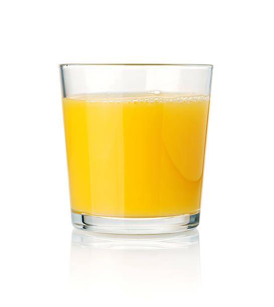 Tumbler glass of orange juice resting on a white surface stock photo