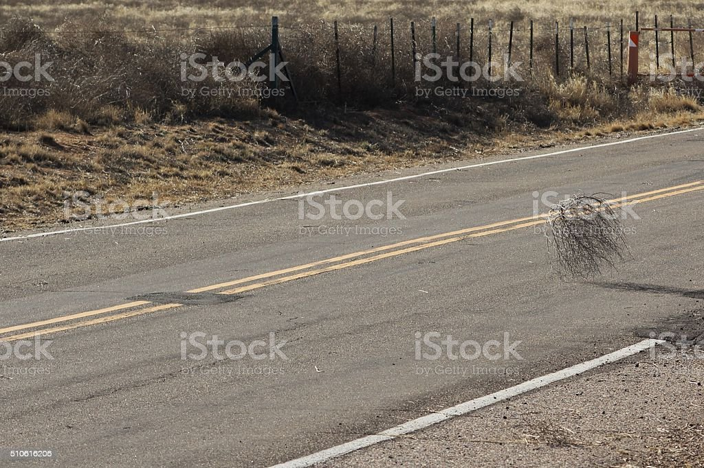 Tumbleweed Blowing Across Empty Road stock photo
