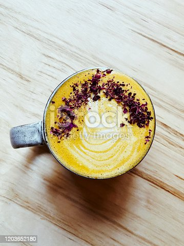 Beautiful turmeric latte with flowers and latte art.