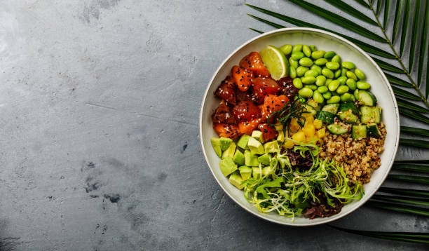 Tuna and Salmon Poke bowl Raw fish salad Asian trendy food with soy beans edamame, quinoa, avocado, pineapple, cucumber and lettuce in bowl on concrete background copy space stock photo
