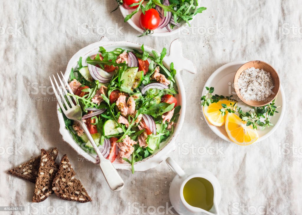 Tuna, arugula, tomato, cucumber salad with mustard dressing. Healthy diet food. Mediterranean style. On a light background, top view stock photo