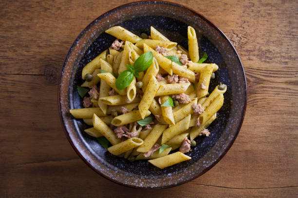 Tuna, basil and caper penne with pesto sauce in bowl on wooden background Tuna, basil and caper penne with pesto sauce in bowl on wooden background. Pasta with tuna fish. overhead, horizontal tuna animal stock pictures, royalty-free photos & images