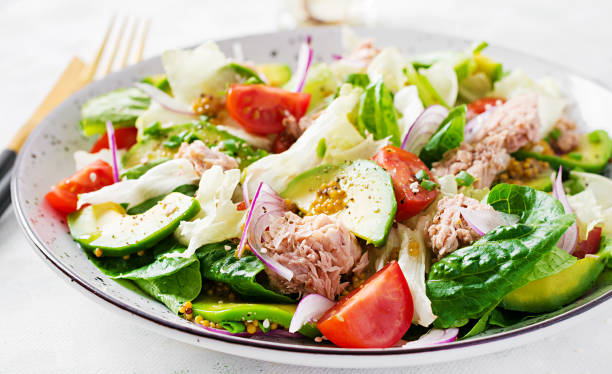 Tuna fish salad with lettuce, cherry tomatoes, avocado and red onions. Healthy food. French cuisine. stock photo