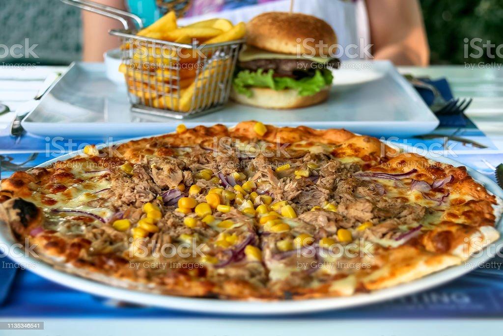 Tuna pizza and cheeseburger stock photo