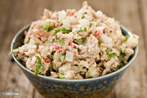 A high angle close up shot of a blue ceramic bowl full of freshly made tuna salad. Shot on an old wooden background.