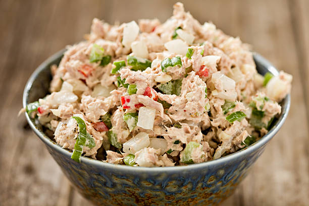 Tuna Salad A high angle close up shot of a blue ceramic bowl full of freshly made tuna salad. Shot on an old wooden background. tuna animal stock pictures, royalty-free photos & images