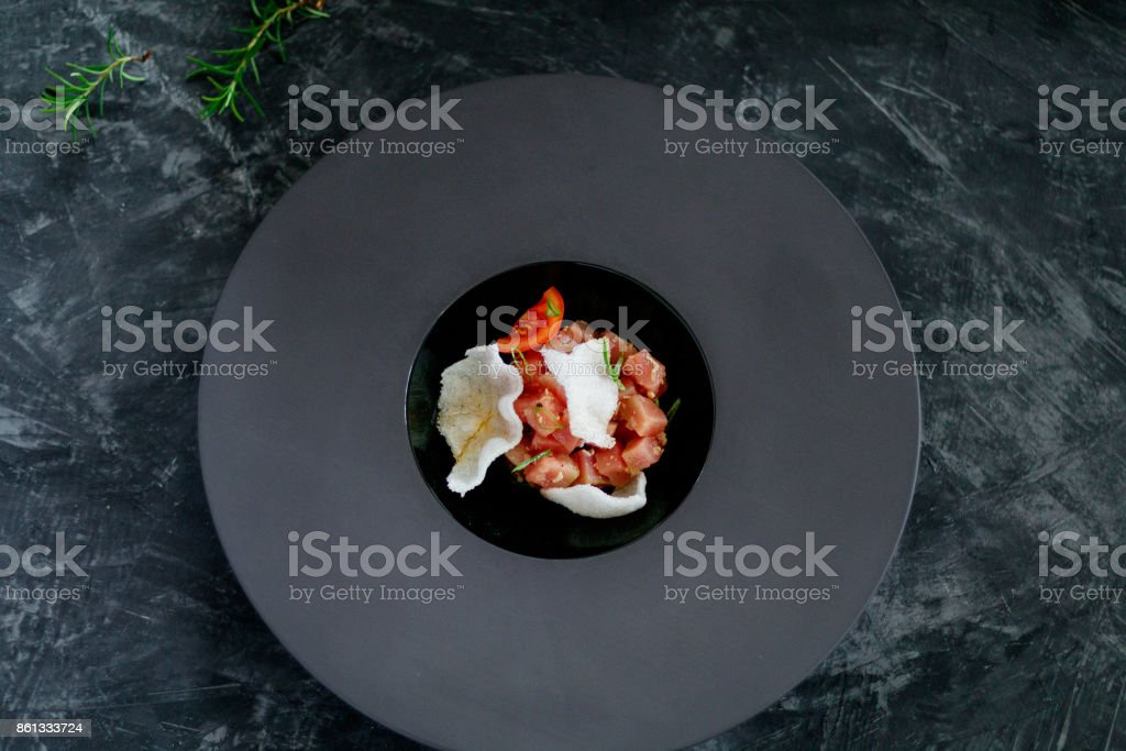 Tuna salad with chips in a black plate stock photo